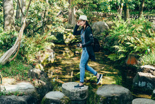Full Length Of Young Girl Walking In Nihon Teien On Sunny Day. Lady Photographer Travel In Osaka With Slr Camera Jumping On The Rock Above The Pond In Japanese Garden. Asian Woman Standing Near Water