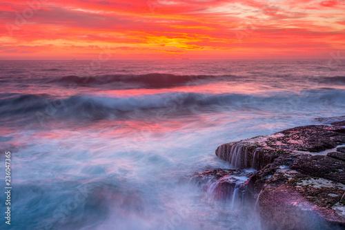 Fotografija  Res skies over ocean as waves surge over rocks