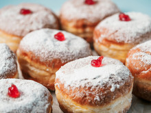 Hanukkah Food Doughnuts With Jelly And Sugar Powder On Blue Background. Jewish Holiday Hanukkah Concept And Background. Copy Space For Text. Shallow DOF