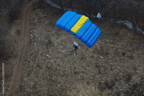 Base jumper with parachute at low altitude before landing. Basejumping.