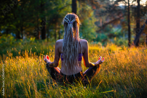 Fotografie, Obraz  Yoga woman silhouette in Lotus pose on a picturesque glade in a green forest