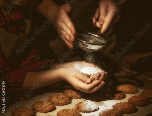 Hands of mother and daughter preparing biscuits