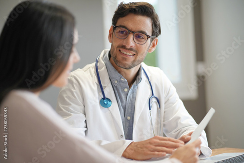 Carta da parati  Modern young doctor speaking to patient in office