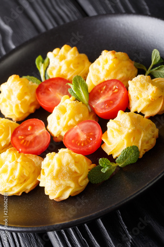 Delicious Duchess potatoes served with mint and tomato close-up on a black plate. vertical