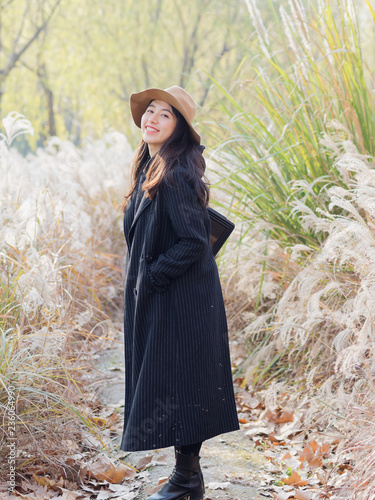 Fotografía  Beautiful young brunette woman in black coat and hat looking and smiling