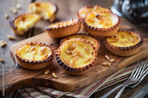 Leinwand Poster Homemade custard tarts with pine nuts on rustic wooden cutting board