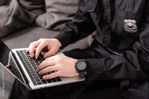 Fototapeta cropped view of policeman typing on laptop keyboard