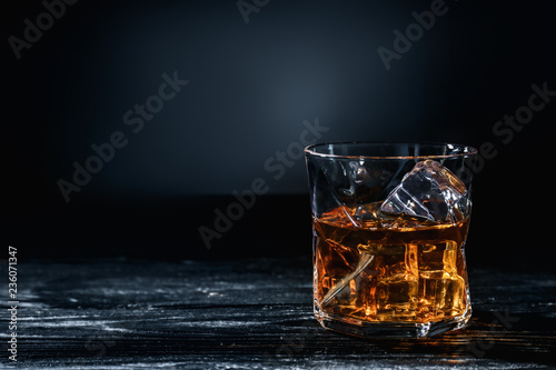 Glass of whisky with ice on wooden table against dark background Canvas