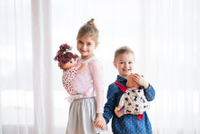 A Portrait Of Two Small Girls Standing And Carrying Dolls In Baby Carriers Indoors.
