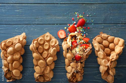 Fotografía  Delicious sweet bubble waffles on color wooden table