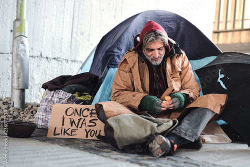 Photo Homeless beggar man sitting outdoors in city asking for money donation