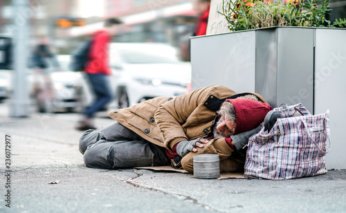 Homeless beggar man lying on the ground outdoors in city asking for money donation Wallpaper Mural
