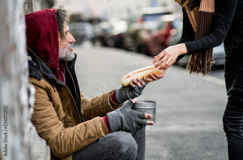 Unrecognizable woman giving food to homeless beggar man sitting in city Fototapeta