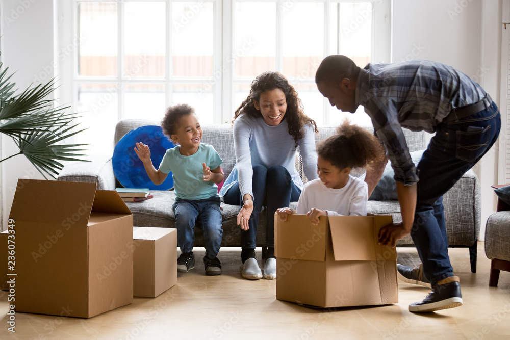 Fototapety, obrazy: Happy playful large African American family moving in new apartment, little preschooler daughter sitting in cardboard boxes, father rolling her to mother, playing together, purchase property concept