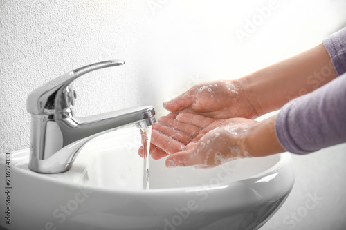 Obraz na plátně Woman washing hands in bathroom