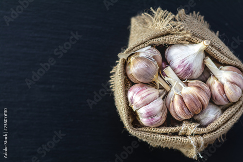 Fotografía  Fresh garlic on a black stone surface, top view, copy space