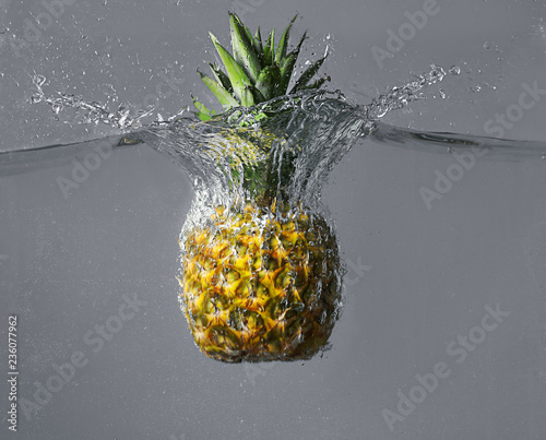 Staande foto Opspattend water Falling of pineapple into water on grey background