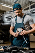 portrait of auto mechanic in uniform with lug wrench at auto repair shop