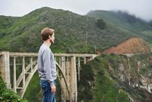 Man Standing In Front Of Bridg...
