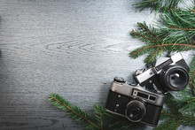 Top View Of Vintage Camera Between Christmas Tree, On Wooden Texture, Copy Space