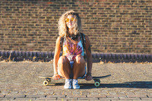 Young Woman Sitting On A Skate...