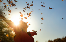 Woman Throwing Autumn Leaves O...