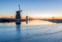 Scenic View Of River With Windmills During Sunset