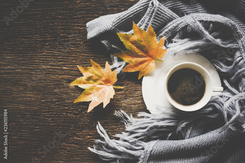 Cozy winter background, cup of hot coffee with marshmallow, warm knitted sweater on old wooden background, vintage tone. Lifestyle concept