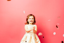Portrait Of An Excited Small Toddler Girl With A Big Smile, Isolated On Pink Studio Background