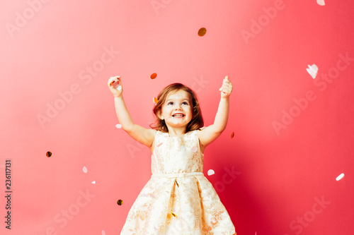 Studio shot of toddler girl throwing confetti