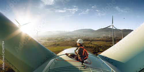 Happy engineer feel success after good work. He standing a top of windmill and looking beautiful sunset landscape