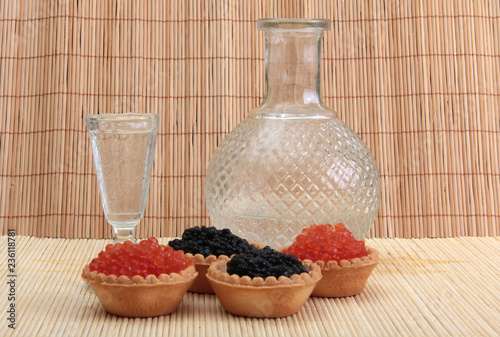 Fish caviar in a plate on a wooden background