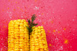 Leinwanddruck Bild - Yellow sweet corn with spices on red background. Minimal food concept.