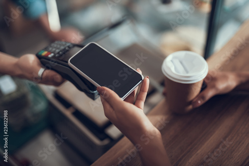 Fotografie, Obraz  Hand of young lady placing smartphone on credit card payment machine