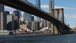 Wide shot of the Brooklyn Bridge on the Brooklyn side with New York City in the background.