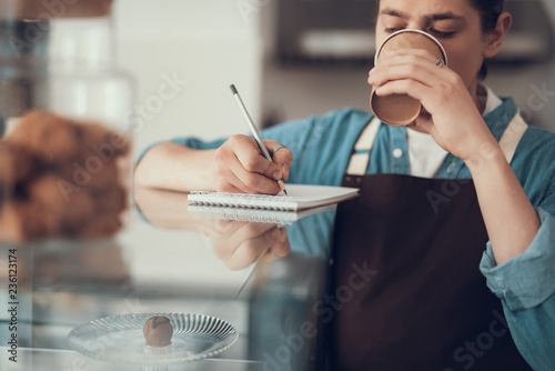Fotografia  Calm barista drinking coffee and making notes in notebook