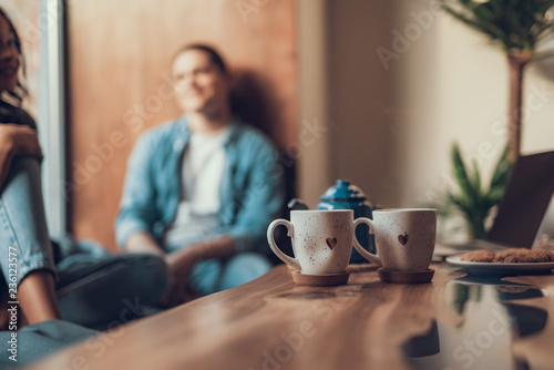 Calm people relaxing near the window while their cups of tea with lovely hearts standing on the table