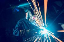 London, England, 02/02/2018 A Vibrant Action Shot Of A Skilled Working Metal Welder In Action, Welding Metal. Photographed With A Slow Shutter Speed And Spark Trails. Orange And Teal.