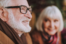 Close Up Side View Portrait Of Senior Man In Glasses Looking Away And Smiling. Old Lady On Blurred Background