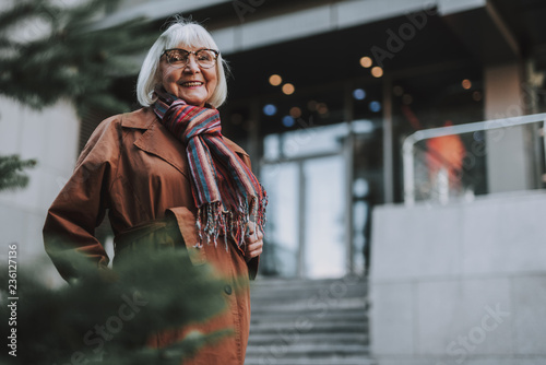Waist up portrait of charming old lady in coat looking at camera and smiling. Copy space in right side