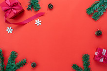 Table Top View Of Merry Christmas Decorations & Happy New Year Ornaments Concept.Flat Lay Essential Difference Object Fir Tree And Gift Box & Snow Ice On Modern Red Paper Background.copy Space Design.