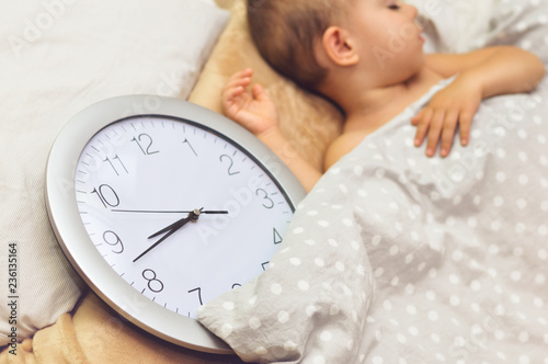 Fotografie, Obraz  Cute two year old baby boy sleeping in his bed with a clock which shows 15 minutes to nine