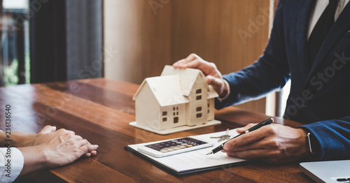Fototapeta Real estate broker agent presenting and consult to customer to decision making sign insurance form agreement, home model, concerning mortgage loan offer for and house insurance obraz