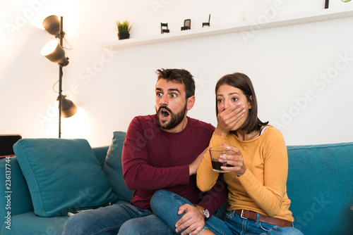 Couple watching TV, movie night with surprised faces, girl holding her hand on the mouth Tablou Canvas