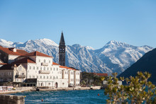 Winter In Montenegro. Perast In The Bay Of Kotor With Snow Peaks Of Mountains, Blue Cold The Adriatic Sea, Old Town With Ancient Architecture, Stone Houses And Tiled Roofs.