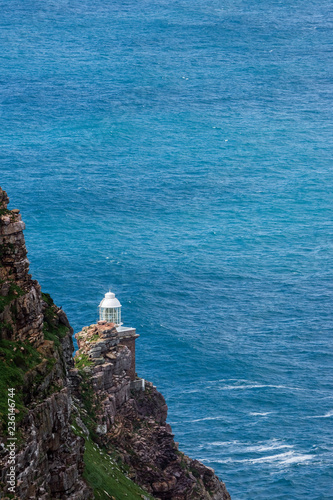 Fotografering  Old Cape Point Lighthouse against blue ocean water