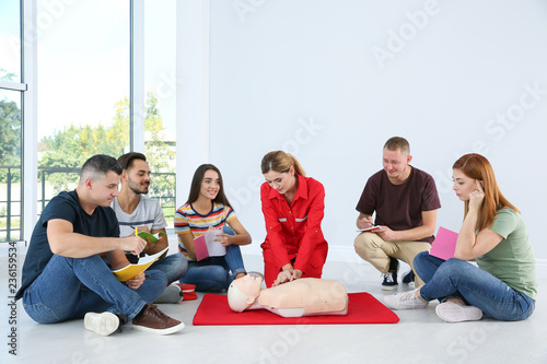 Instructor demonstrating CPR on mannequin at first aid class indoors