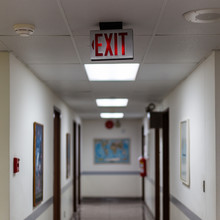 Red Emergency Exit Sign In The Dark Room. Illuminated Office Exit Sign.