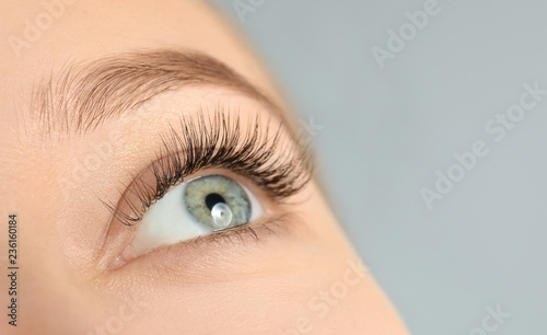 Young woman with beautiful long eyelashes on gray background, closeup Poster Mural XXL