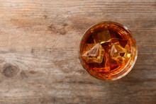 Golden Whiskey In Glass With Ice Cubes On Wooden Table, Top View. Space For Text